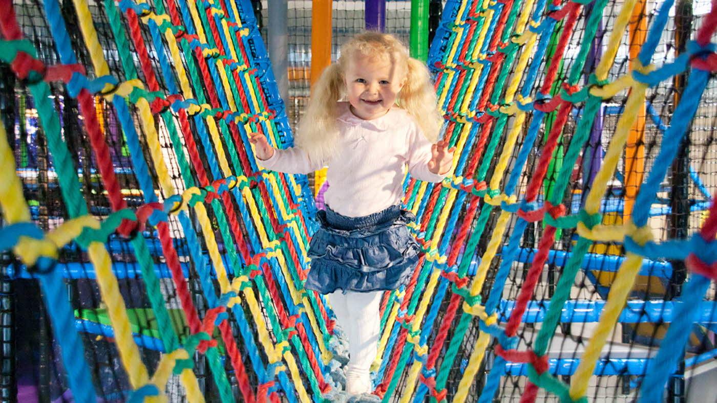 Jente klatrer i tau som er i forskjellige farger