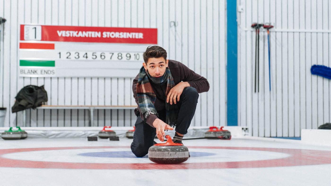 mann som spiller curling